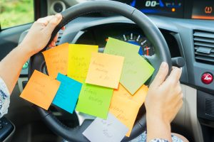 woman driving notes covering steering wheel