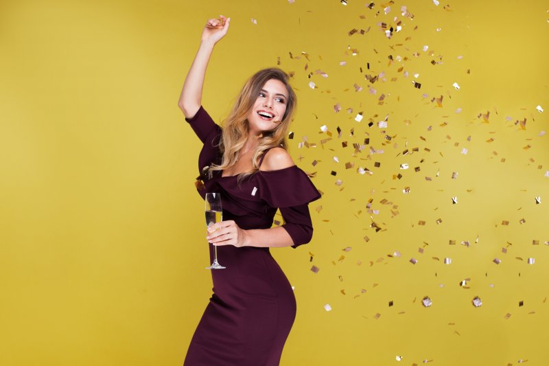 A woman celebrating and holding a wine glass.