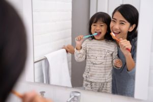 parent brushing their teeth with their child in a bathroom