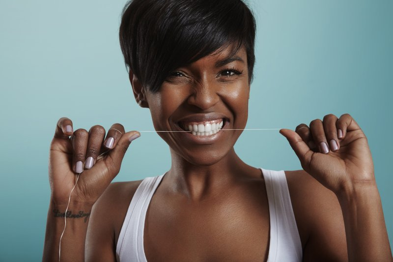 a woman smiling and flossing her teeth